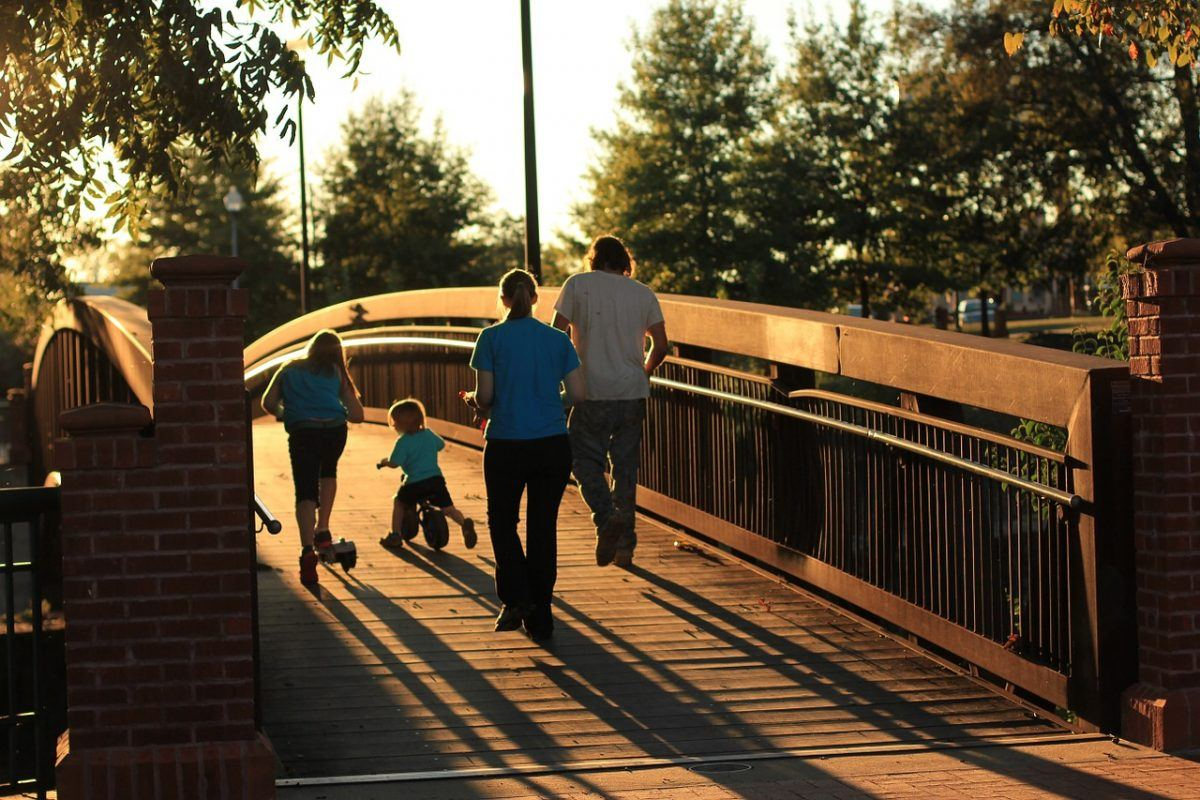 family walking over a bridge wth kids on a tricycle