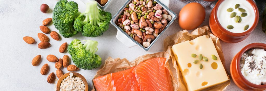A variety of protein foods, including egg, salmon, beef, chicken, beans, lentils, almonds, quinoa, oats, broccoli, artichokes, yogurt, cheese, and tofu