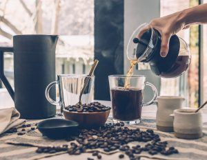 making coffee with coffee beans, a water carafe, and a cup