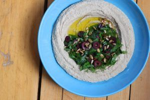 green lentil hummus with a variety of herbs, seeds, and olives, on top of a blue plate on a table