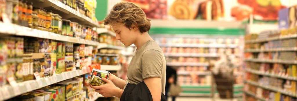 Man reading the labels to compare two jarred products while standing in a supermarket aisle