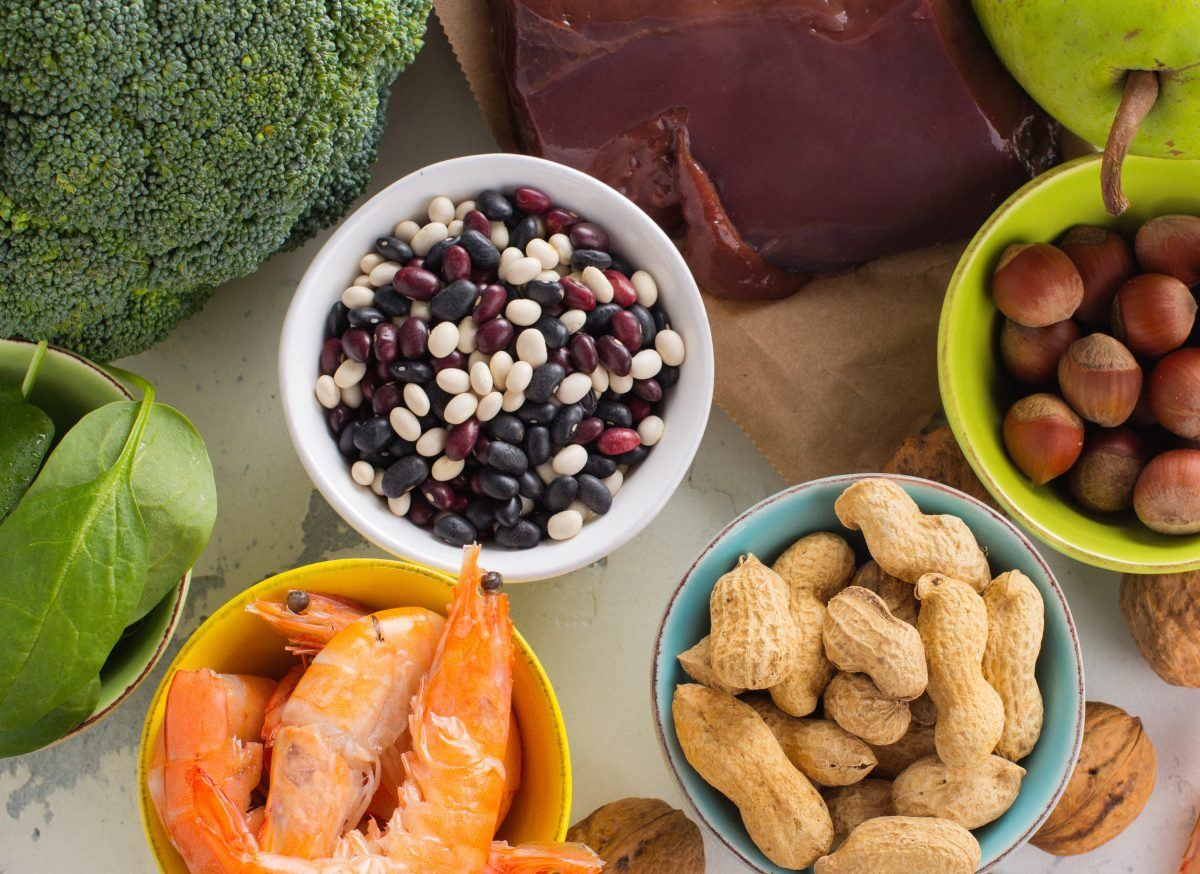 Foods rich in folate (vitamin B9) including beans, broccoli, shellfish, peanuts, liver, nuts, and spinach