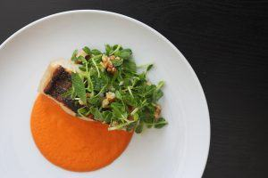 A plate with pan seared bass fish over a bright red walnut romesco sauce and topped with a bright green pea shoot salad