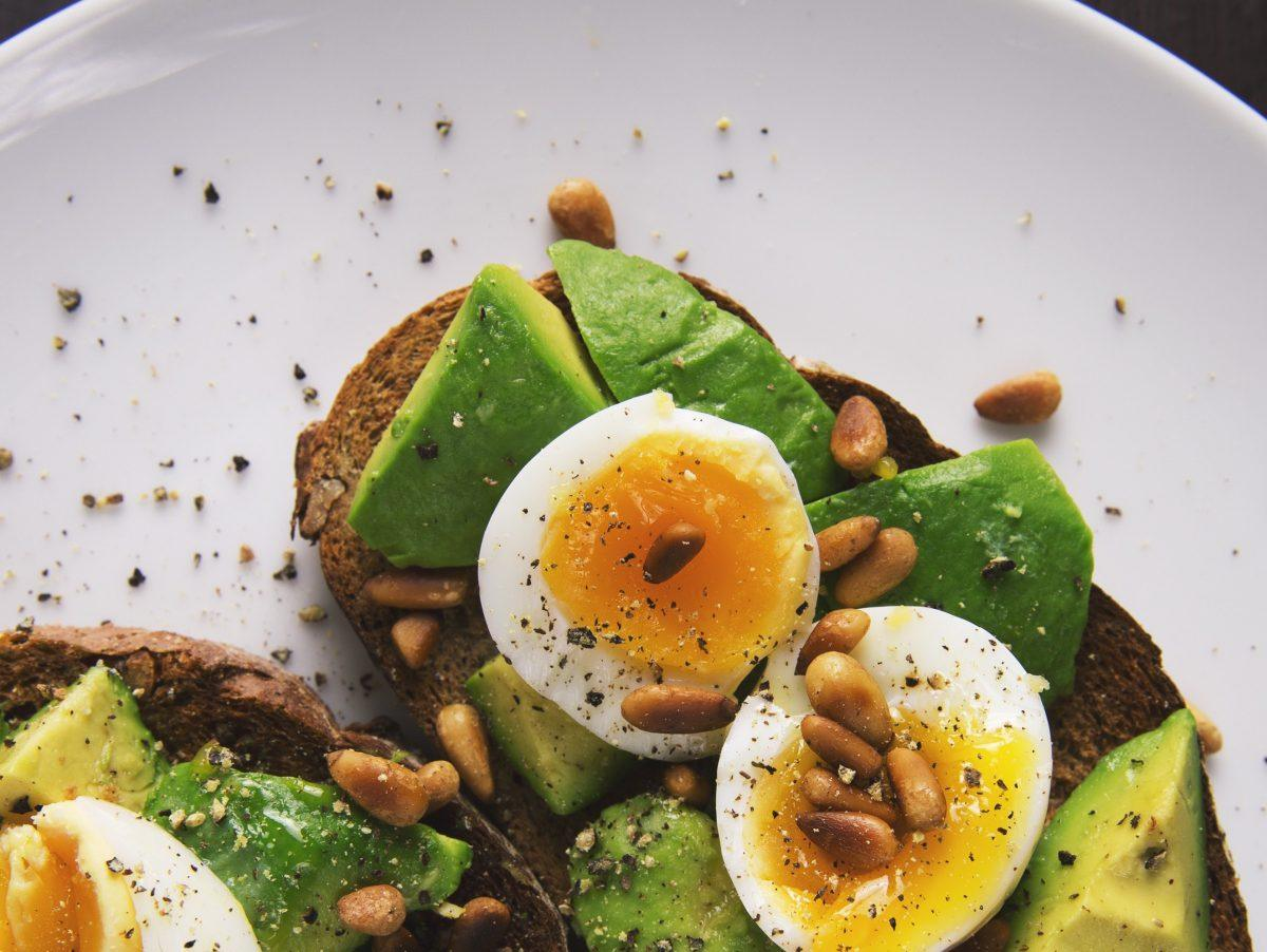 avocado, soft boiled eggs with yolks, and pinenuts on toast