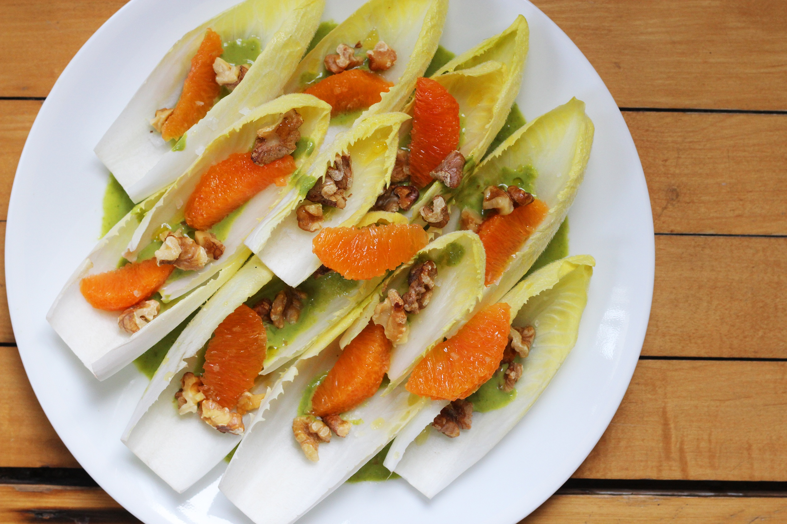Endive leaves topped with cara cara orange segments and toasted walnuts