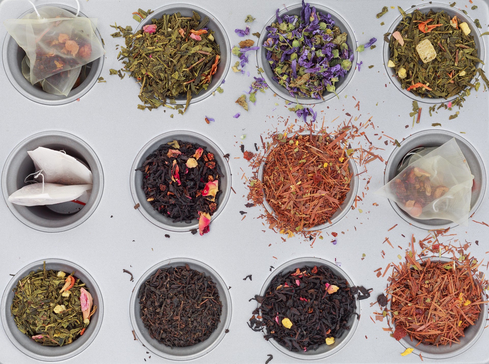 A variety of loose leaf and bagged teas in cups of a baking tray