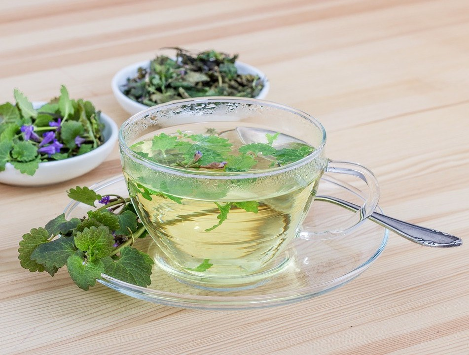 a glass teacup filled with herbal tea made of mint leaves and other herbs and flours in bowls alongside it