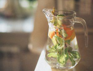 Pitcher of water filled with orange slices and mint leaves