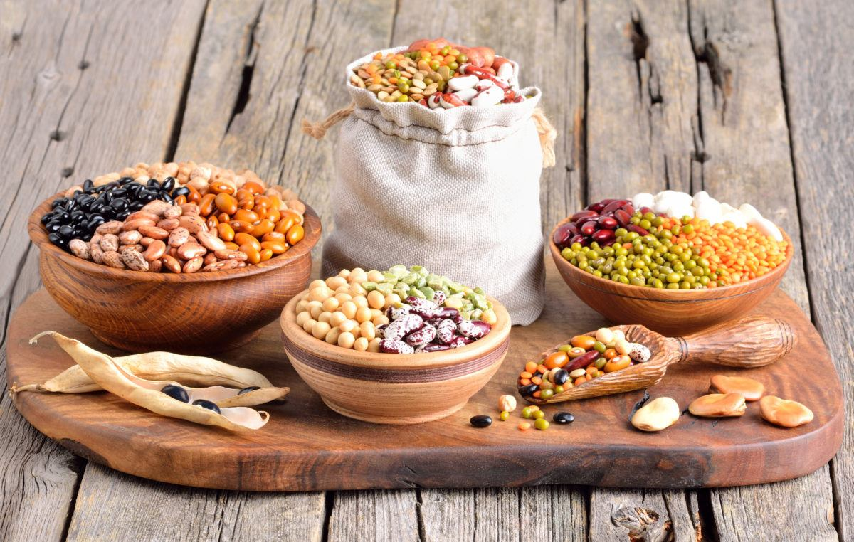 a variety of legumes and pulses organized in bags and bowls on a wooden tray, including black beans, cranberry beans, kidney beans, white beans, split peas, mung beans, yellow lentils, red lentils, green lentils