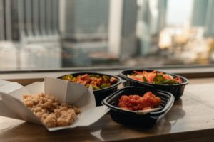 Delivered food in takeout containers, including rice, vegetables, and chicken