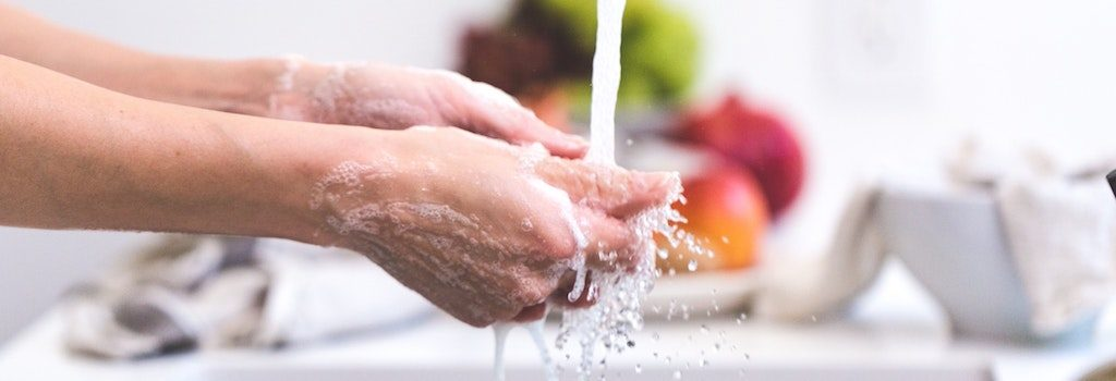 washing hands with soap and water with produce in the background