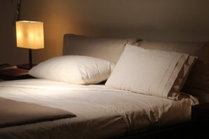 Bed with white sheets and pillow in a dimly lit, calm room for sleeping