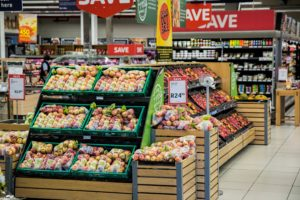 photo of a supermarket aisle with sale signs over the produce section filled with apples