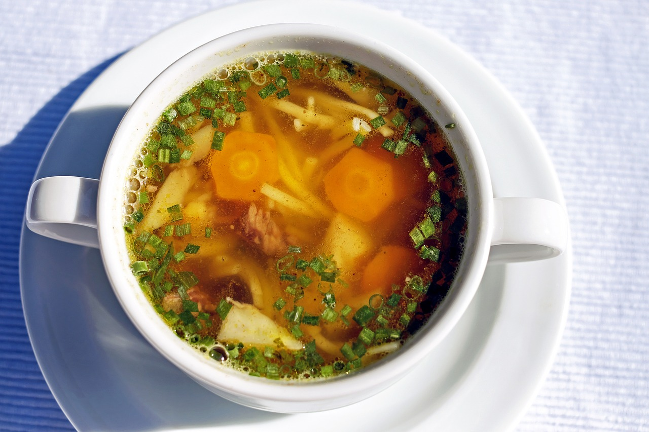 bowl of chicken soup with carrots and broth and parsley