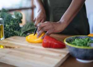 woman chopping yellow and red peppers on a bamboo cutting board alongside a chopped bowl of kale