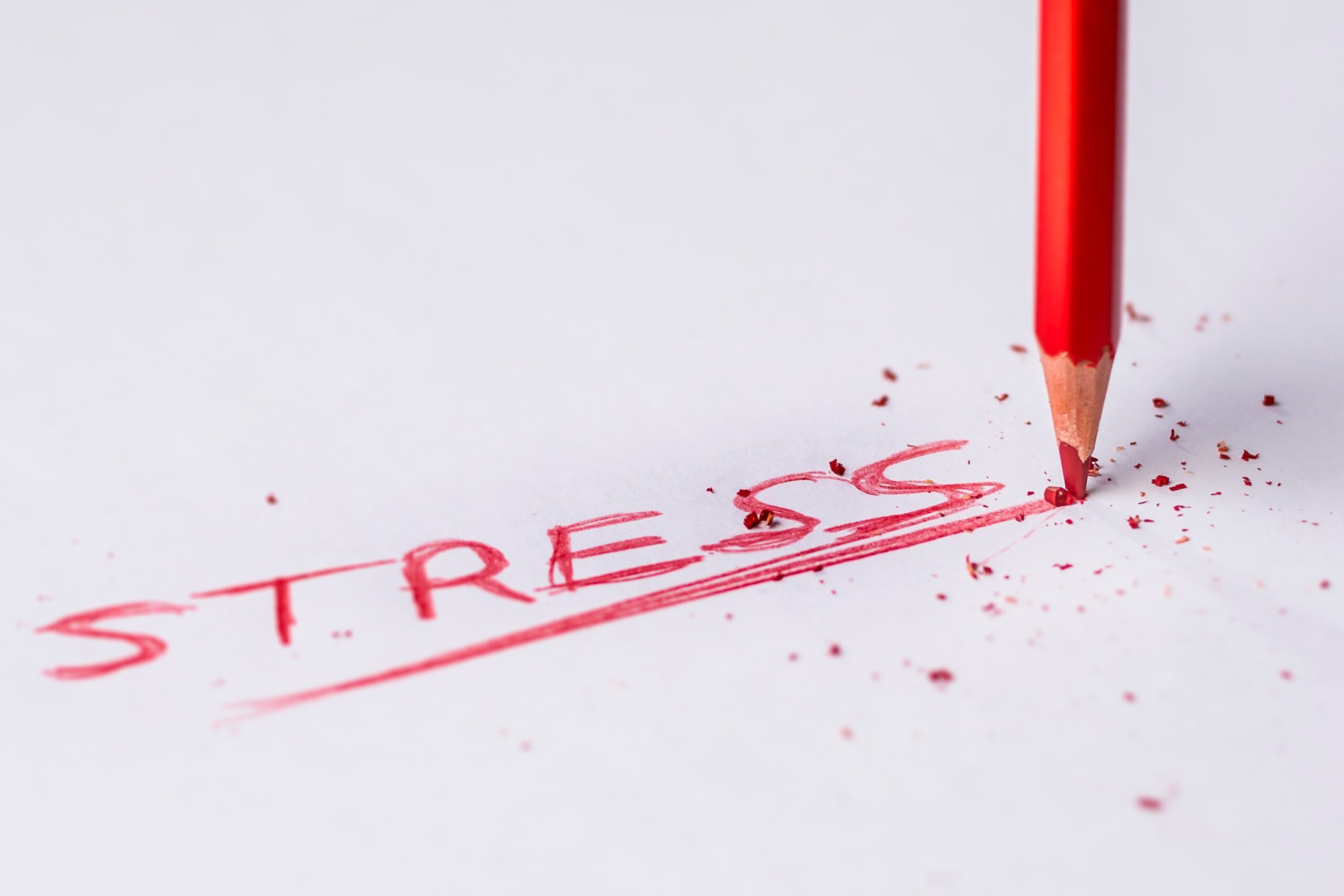the word stress written out in a red colored pencil, with pressure being applied to the pencil causing the tip to break
