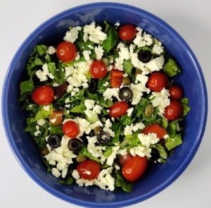 feta cheese sprinkled on top of a tomato, cucumber, olive, and lettuce salad in a blue bowl
