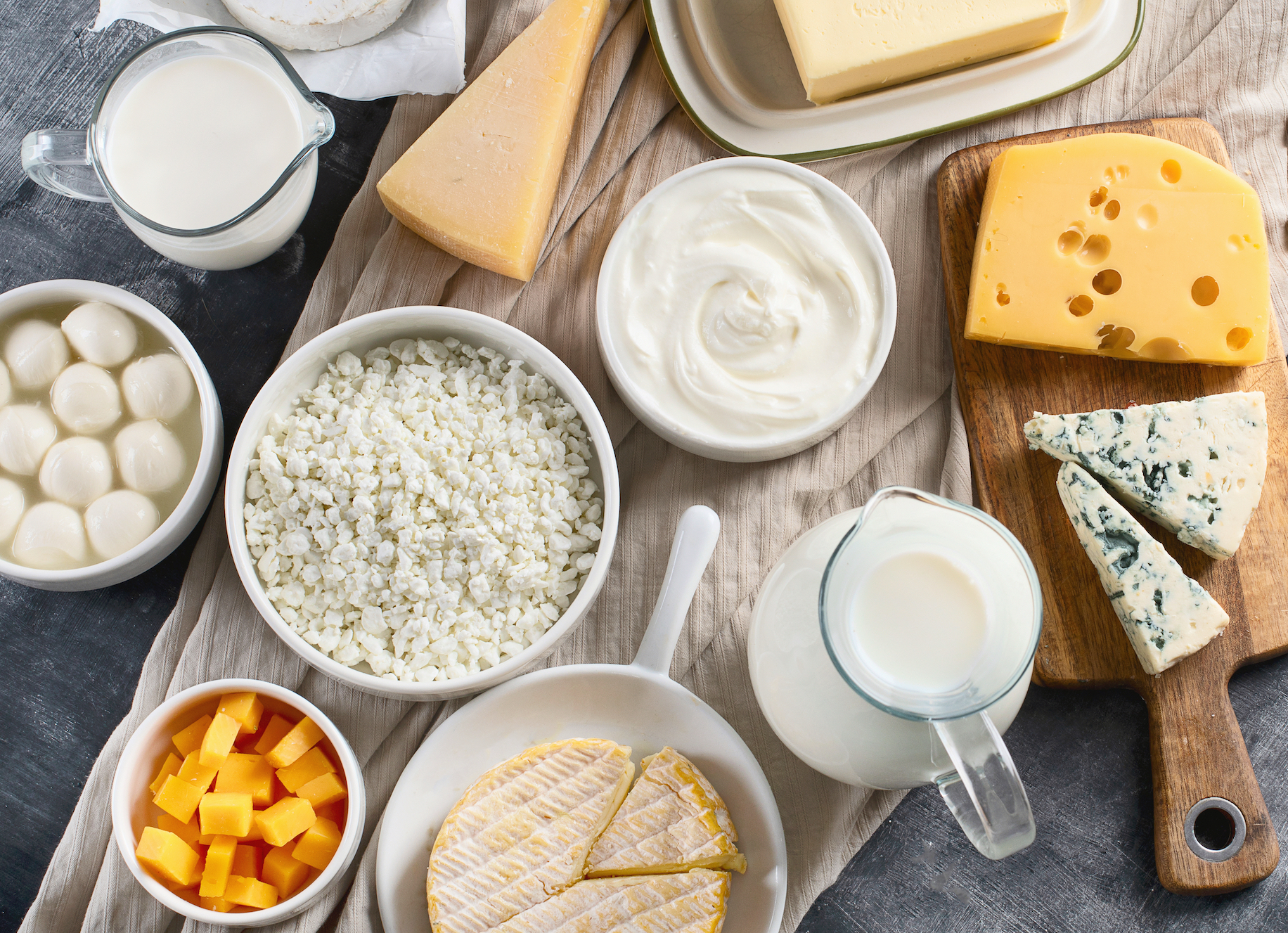 A variety of dairy foods including milk, yogurt and various cheeses including cheddar, swiss, blue cheese, mozzarella, brie