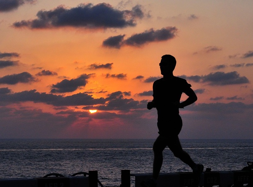 silhouette of man running at dusk amidst background of setting sun in clouds and ocean