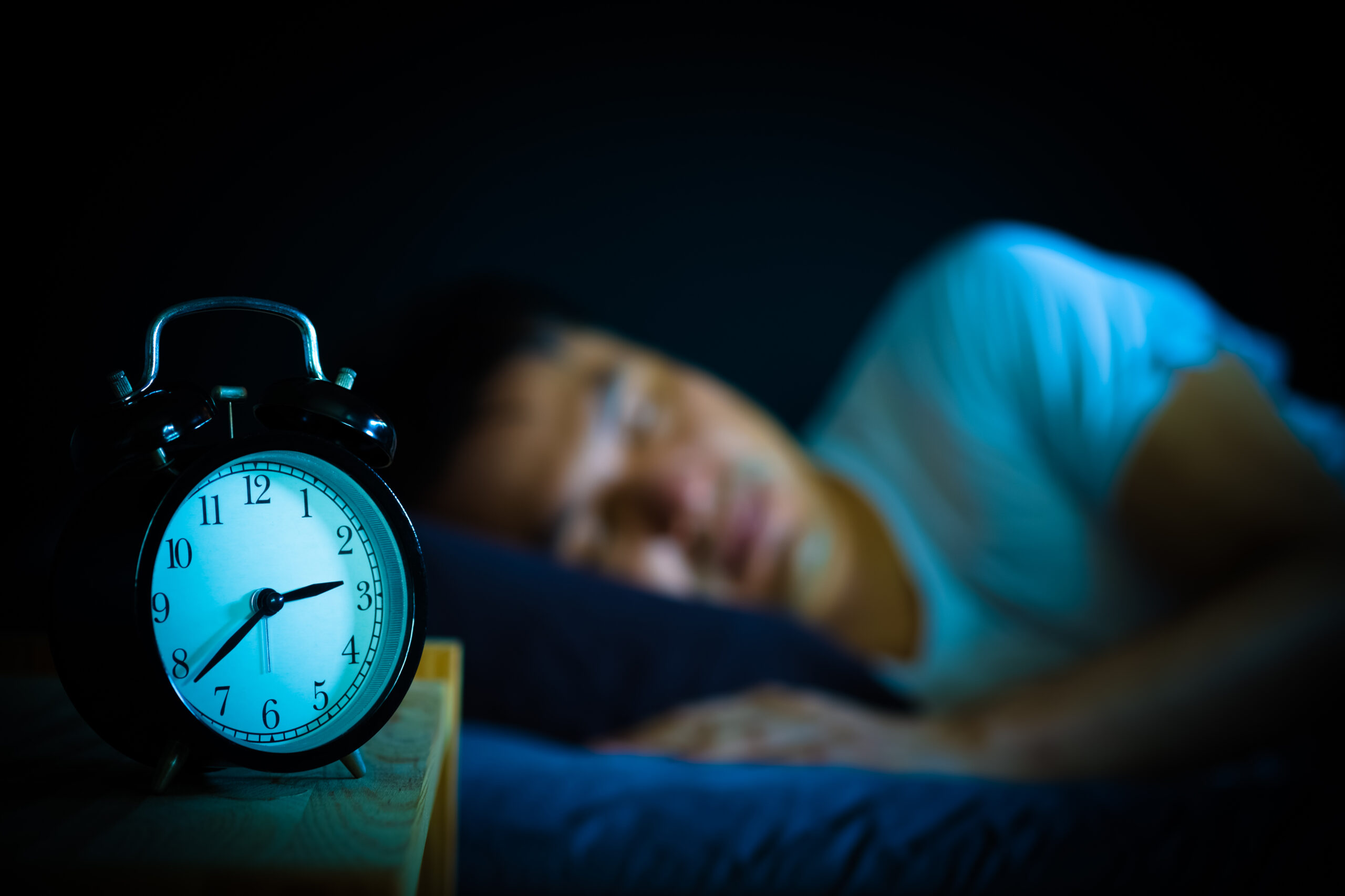 man sleeping in a bed at night with an alarm clock in the foreground showing the time as three am