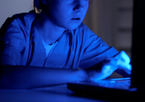 nigh shift nurse sitting at a computer emitting blue screen in the dark