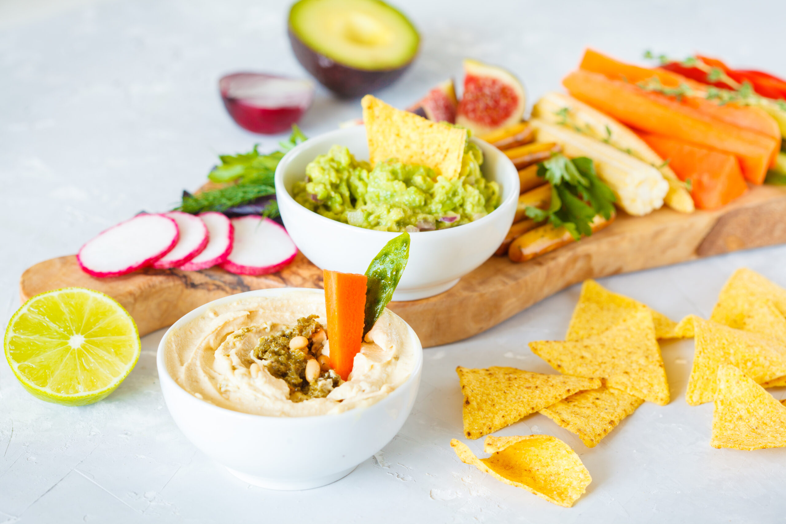 snacks arranged on a board including tortilla chips, hummus, guacamole, and a variety of sliced vegetables and fruits such as carrots, radishes, avocado, and figs