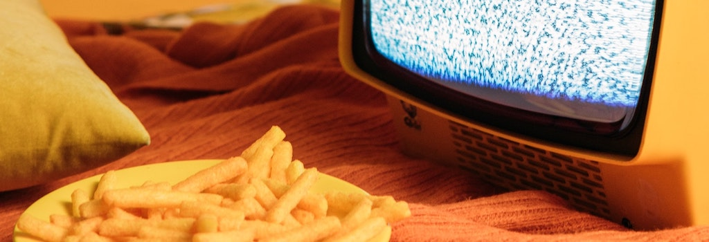 plate of cheese puff snacks next to a television screen to signify advertising junk food