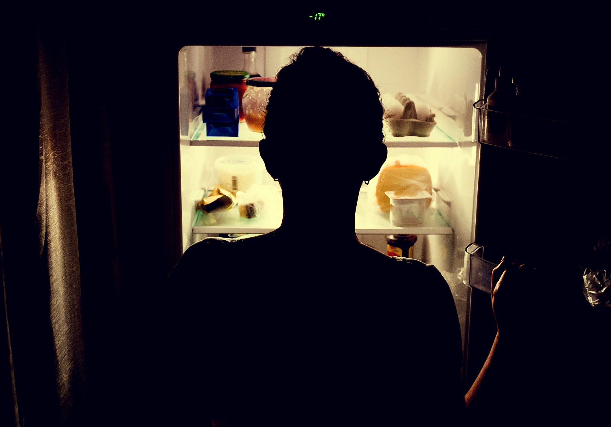 A sillhoutte of a person backlit by the light of a refrigerator, looking for something to eat