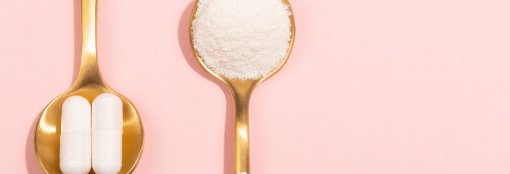 two spoons, one with collagen powder and one with collagen supplements, set on a pink background