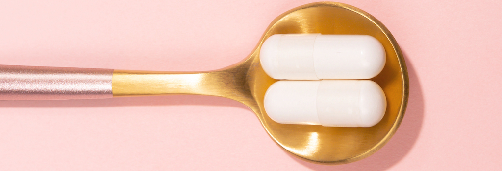 collagen supplements on a gold spoon with pink background