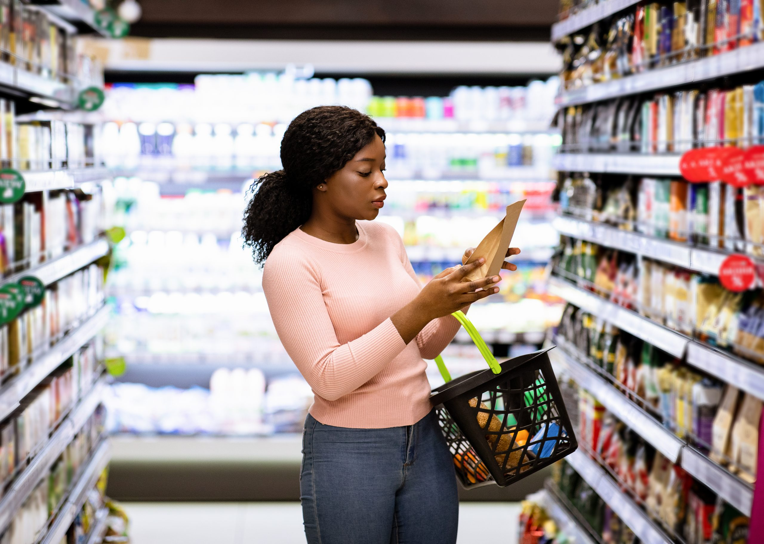 A women grocery shopping and looking at the label on a package of food in her hand