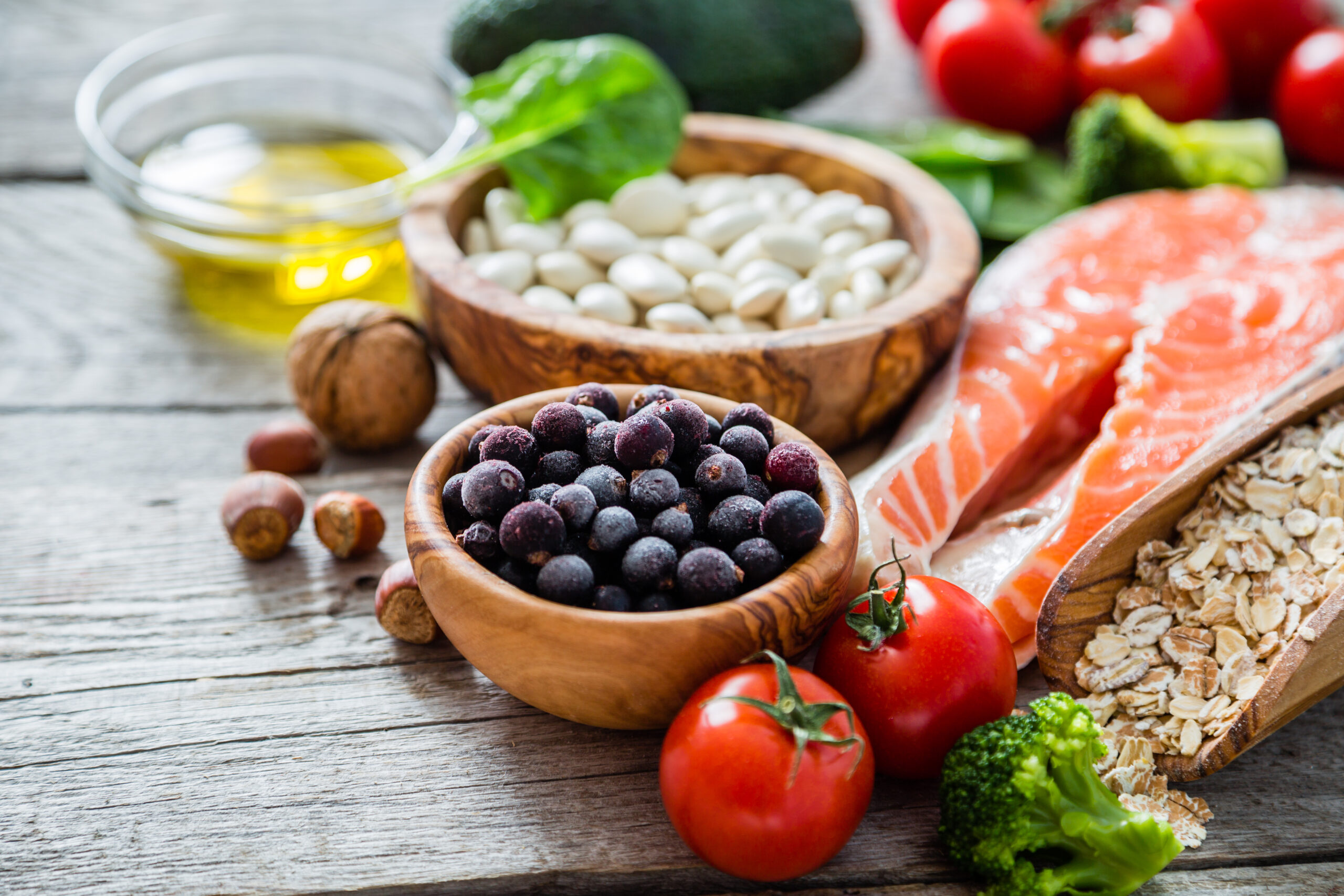 A variety of healthful foods including nuts, beans, berries, tomatoes, broccoli, salmon, and oats
