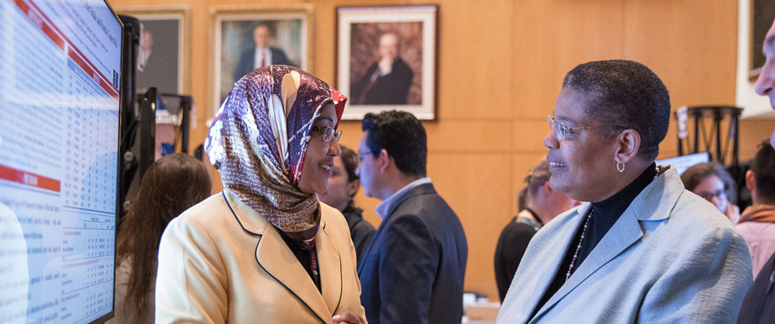 Elkhansa Sidahmed, Yerby Postdoctoral Research Fellow (left), explains her research to Dean Michelle A. Williams at the School's annual poster day in 2016.