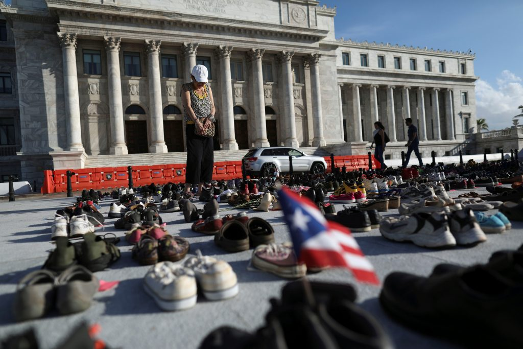 A woman stands among hundreds of pairs of shoes displayed at the Capitol to pay tribute to Hurricane Maria's victims in San Juan