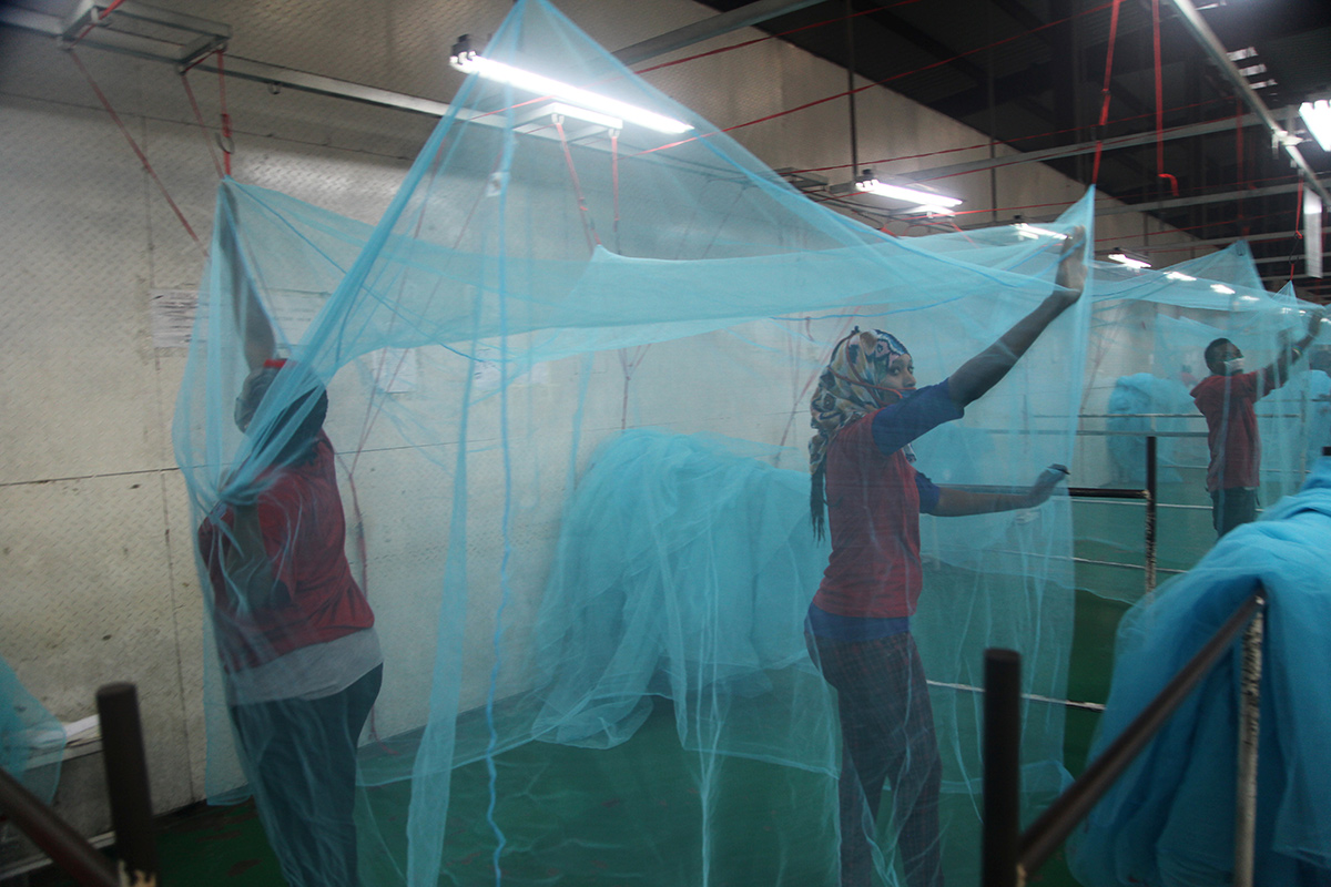 Workers examine insecticide-treated mosquito bed nets in Tanzania