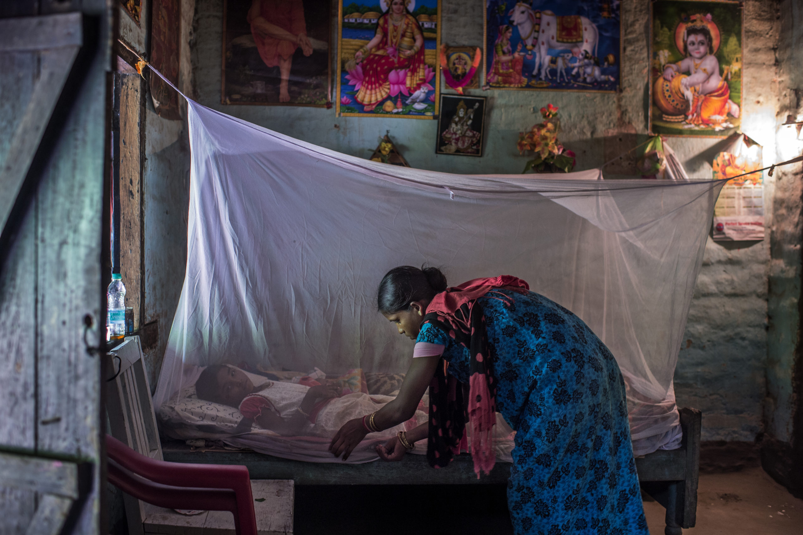 Mino Das adjusts an insecticide-treated bed net in her home in Digaru village, in the northeastern India state of Assam.
