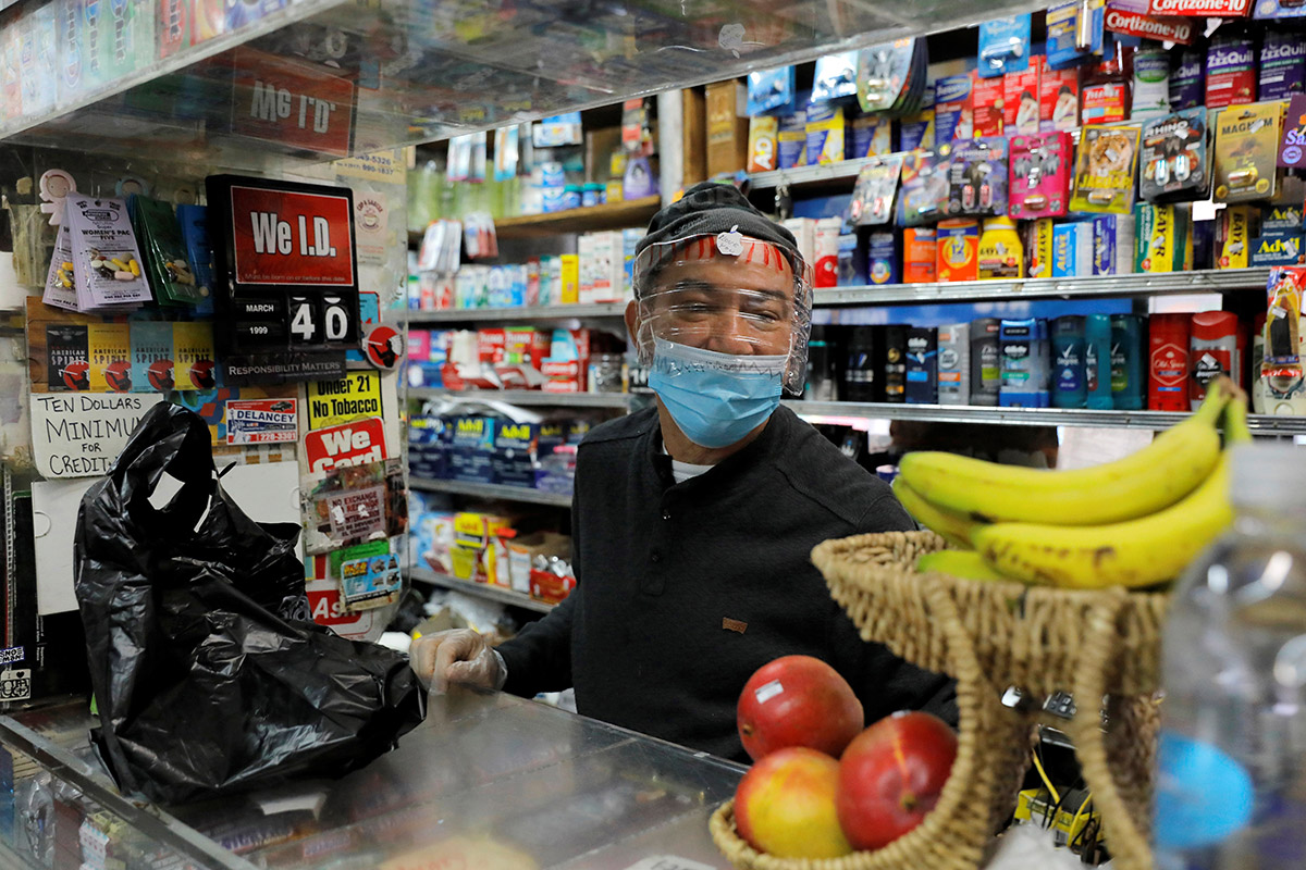 A store clerk pictured behind the counter with a mask and face shield made from a gallon water jug