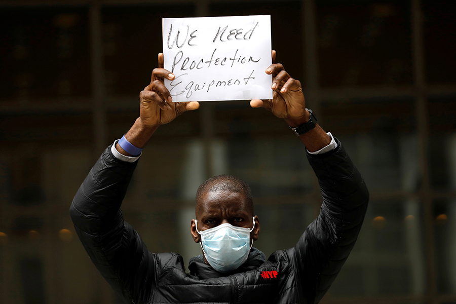 "A Black man wearing a mask holds up a sign reading ""We need protective equipment"""