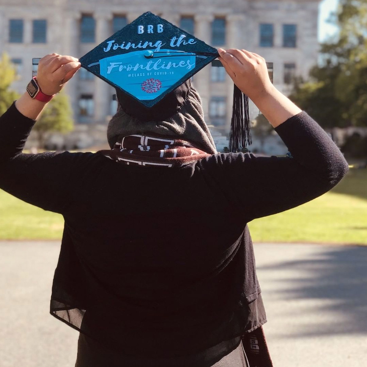 """Photo of Taha Khan from behind to show her graduation cap, which reads """"BRB Joining the Frontlines"""""""