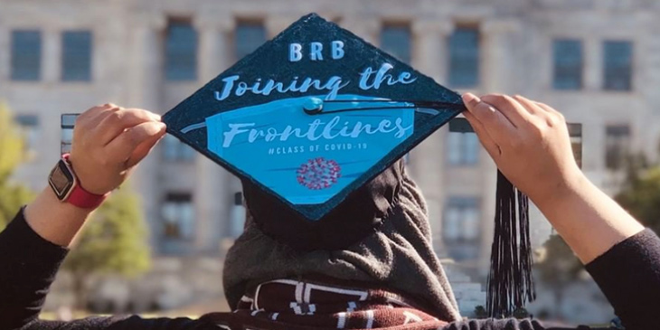 "2020 Graduate pictured from behind with cap that reads ""be right back, joining the frontlines"""