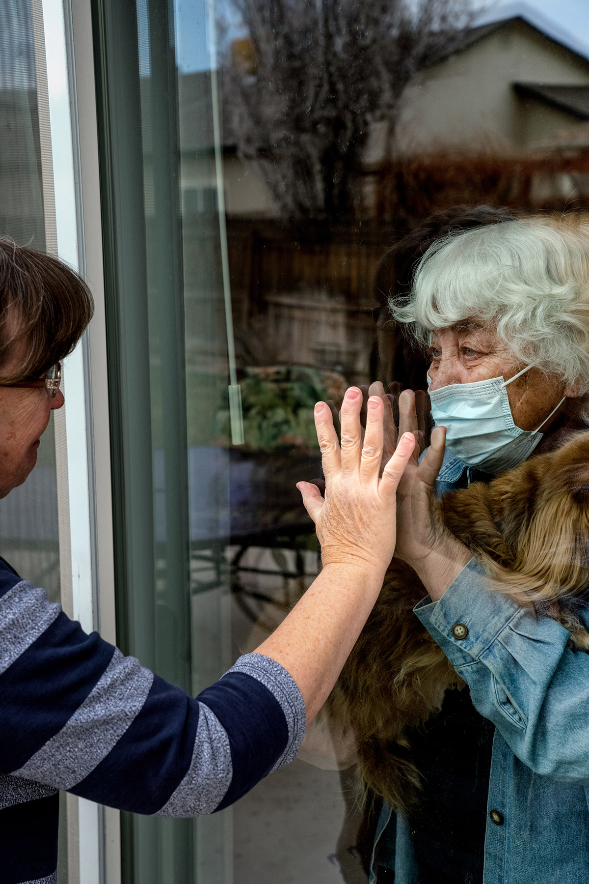Woman touches hands with an elderly woman through a glass window