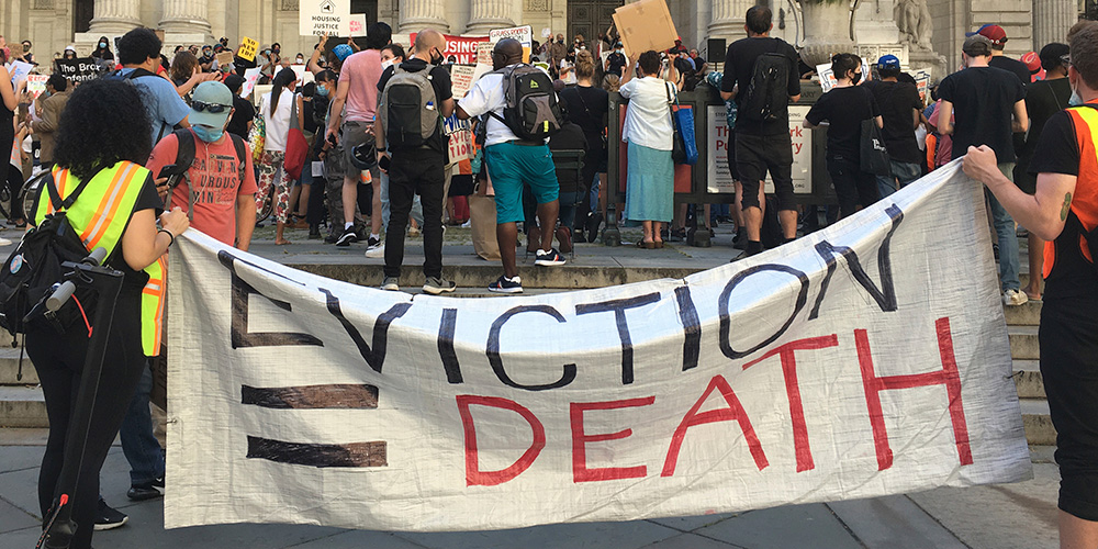 "Photo of protesters holding sign that reads: ""EVICTION = DEATH"""