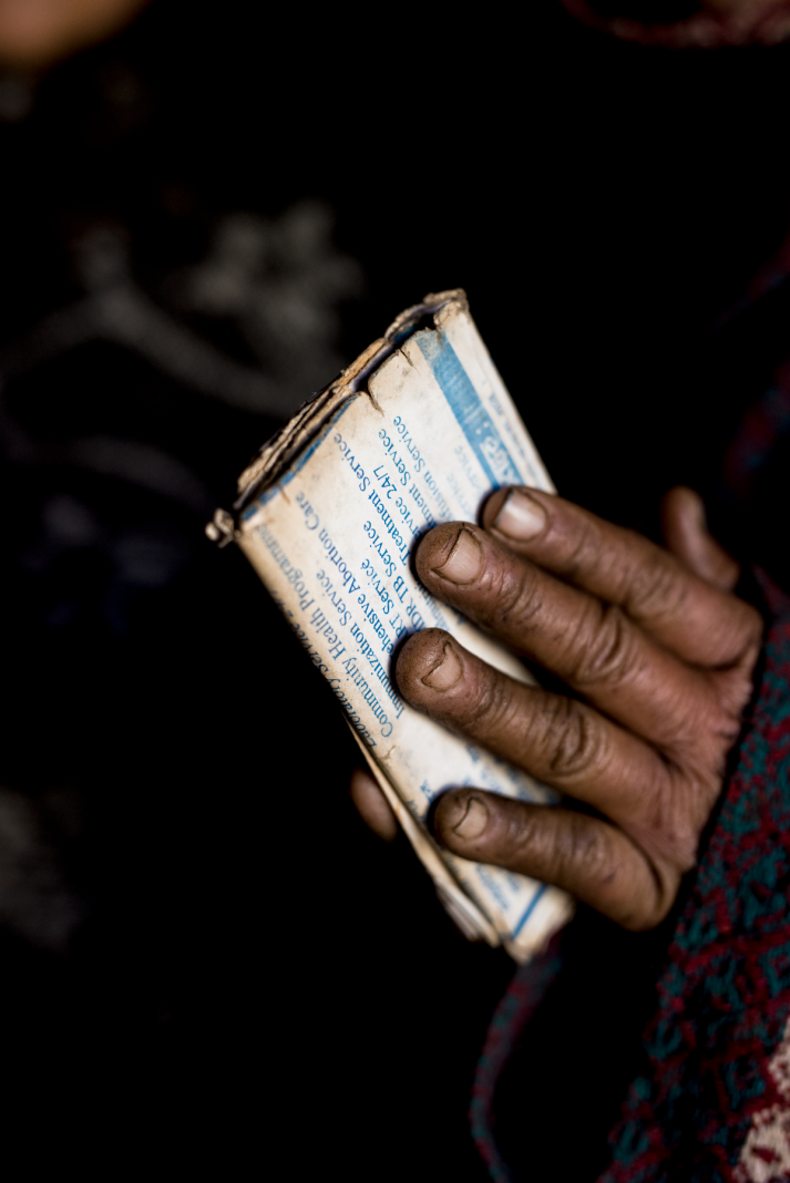 Two dark hands enclose Nepalese medical papers.