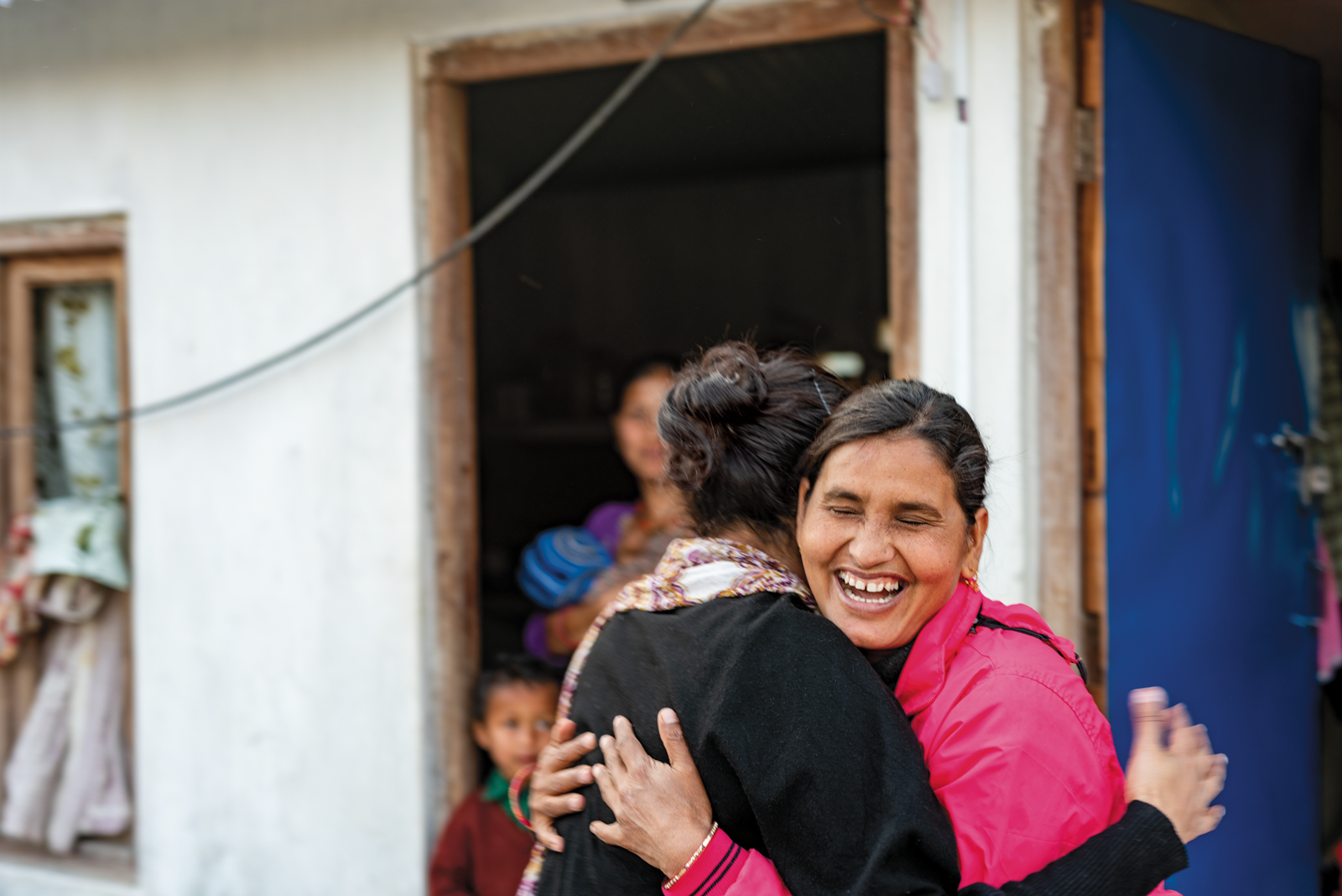 Isha Nirola, wearing a black sweater and white scarf patterned with orange and purple, is embraced by a Nepalese woman wearing a pink top with a big smile. Behind is a Nepalese woman holding a child with a toddler, standing in a doorway.