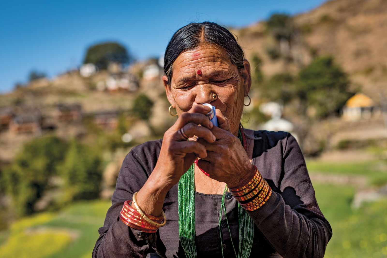 Older Nepalese woman uses an inhaler with both hands in the Nepal countryside. She wears a black greens, green beaded string necklace, mutiple bangles on each wrist, and gold hoop earrings. Learning to use an inhaler outside of Achham