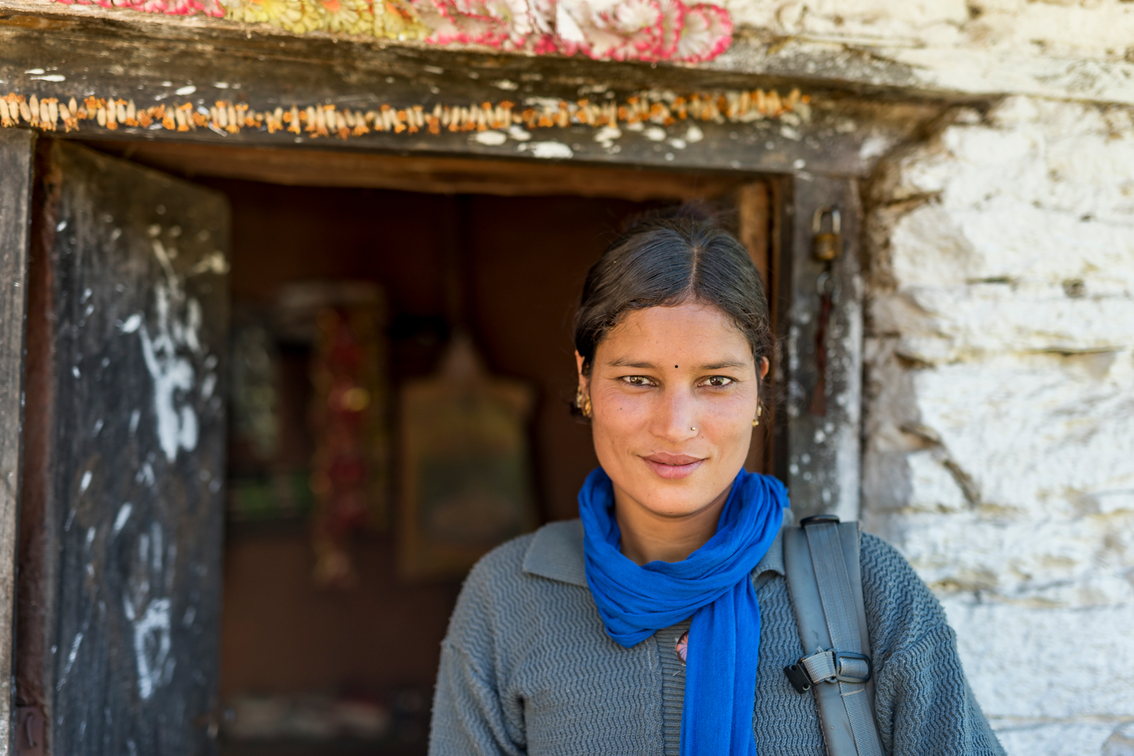 A young female Nepalese woman stands in front of an opn doorway, wearing a blue scarf and grey sweater, with a grey backpack over one shoulder.