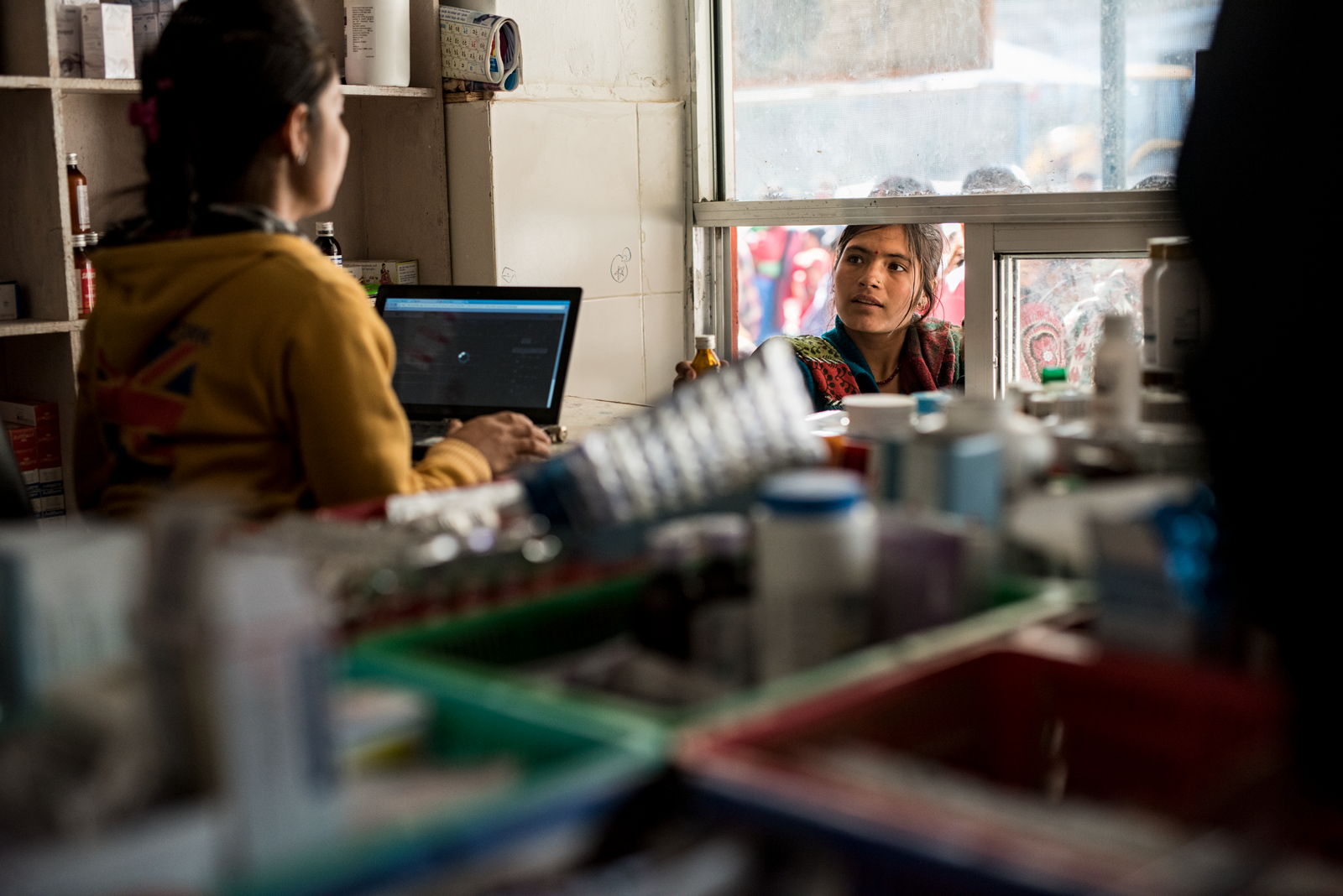 View inside a Nepalese pharmacy window, looking outside. A young woman wearing a teal dress and colored scarf stands outside the sliding window and speaks to a female techniction wearing a yellow hoodie in front of a tablet screen.