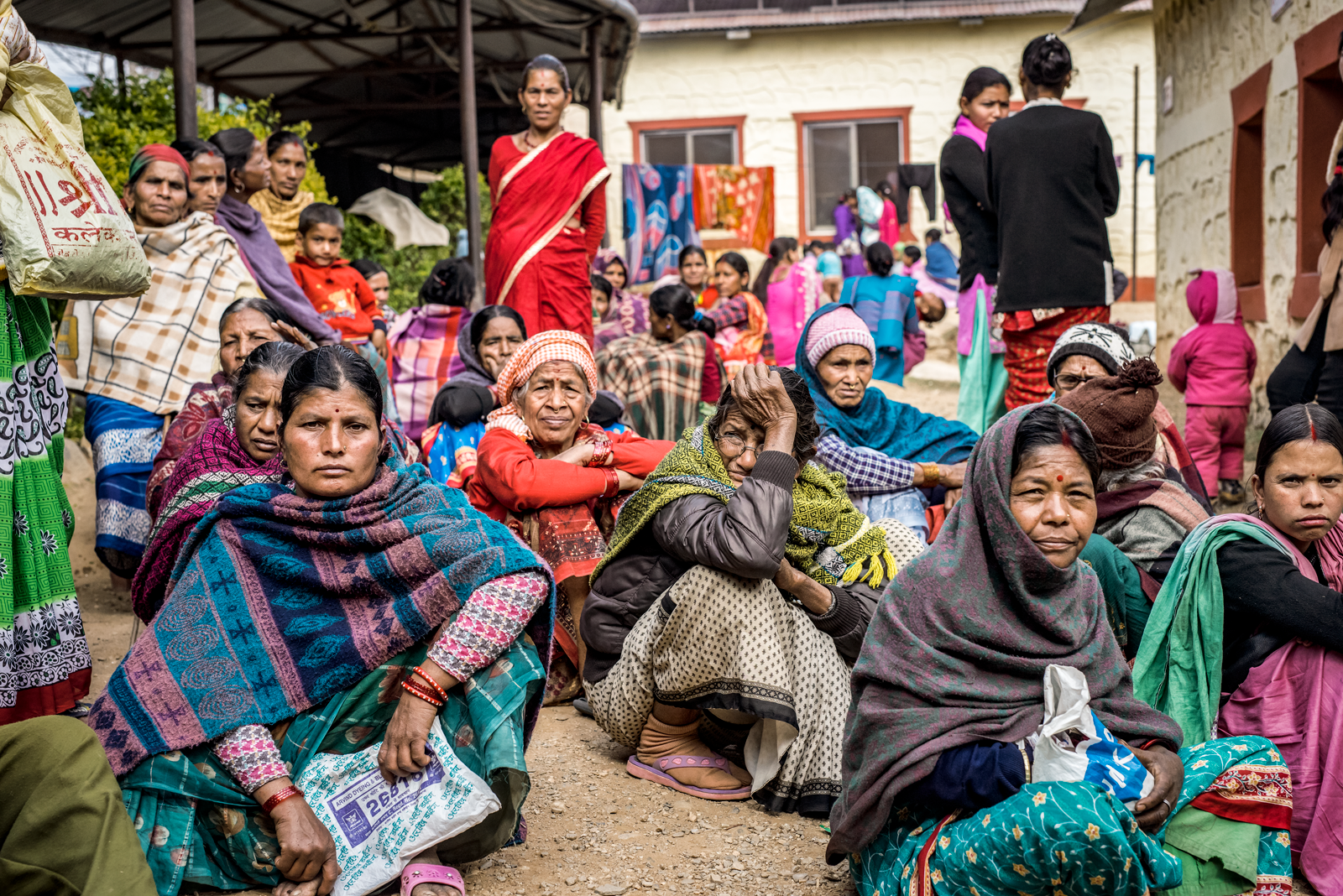 Group of Nepalese women sit in a gravel courtyear, dressed in skirts, brightly colored and patterened woven scarves, and saris.