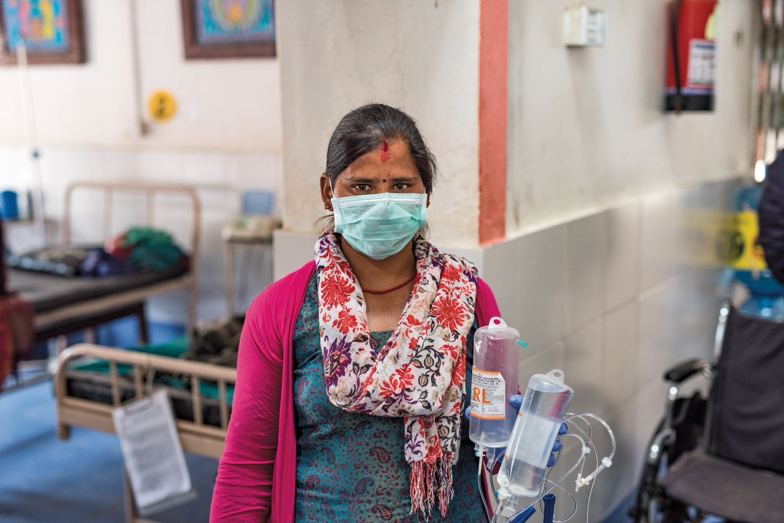 Female nepalese healthcare worker wearing an open, bright pink sweater, paisley teal shirt, white scarf with coral and purple flowers and a disposible mask stands in clinic holding two pouches of saline solution.