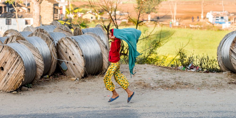 A girl dressed in bright yellow pants, blue sandles, red hoodie runs on a rural gravel road, holding a teal blanket over her head like a cape.